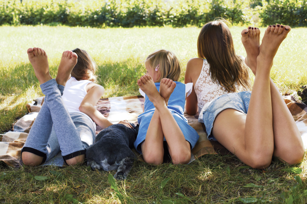happy children lying on green grass outdoors in the grass with dog