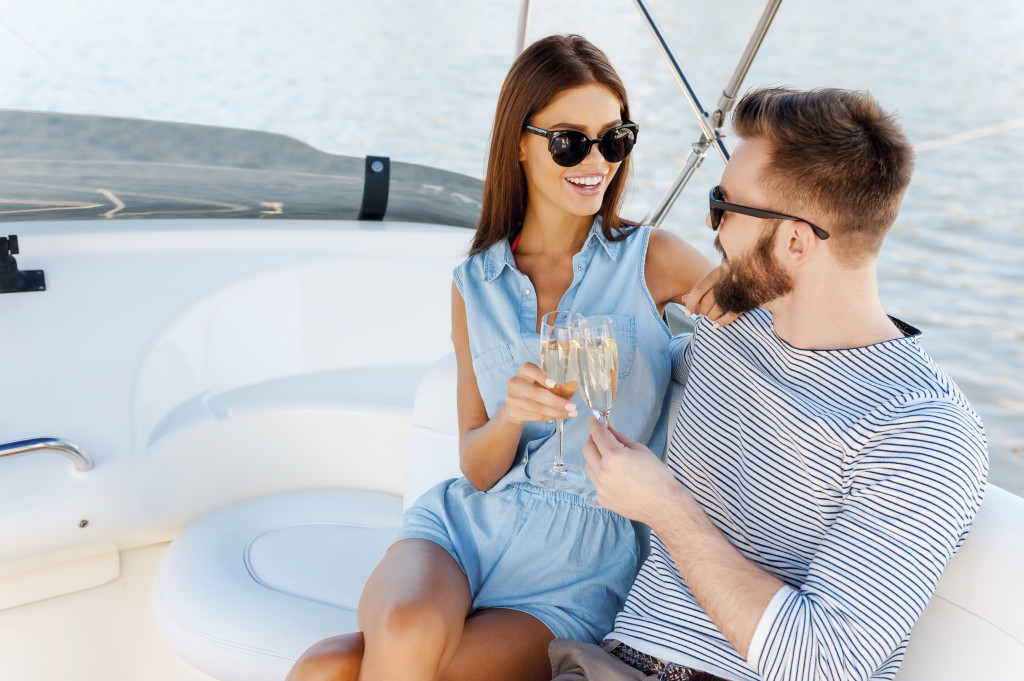 Celebrating their special anniversary. Smiling young couple holding glasses with champagne and looking at each other while sitting on the board of yacht
